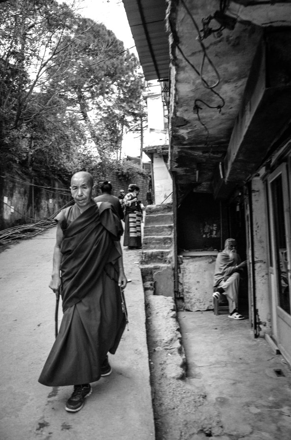 """Love and compassion are necessities, not luxuries. Without them, humanity cannot survive.""― Dalai Lama A Buddhist monk walks through a narrow alley while a Hindu Sadhu sits by a local store along McLeod Ganj. There are over a billion people in India but the tolerance for other religions is fairly strong. Dalai Lama Temple, McLeod Ganj, Dharamsala India November 2015"